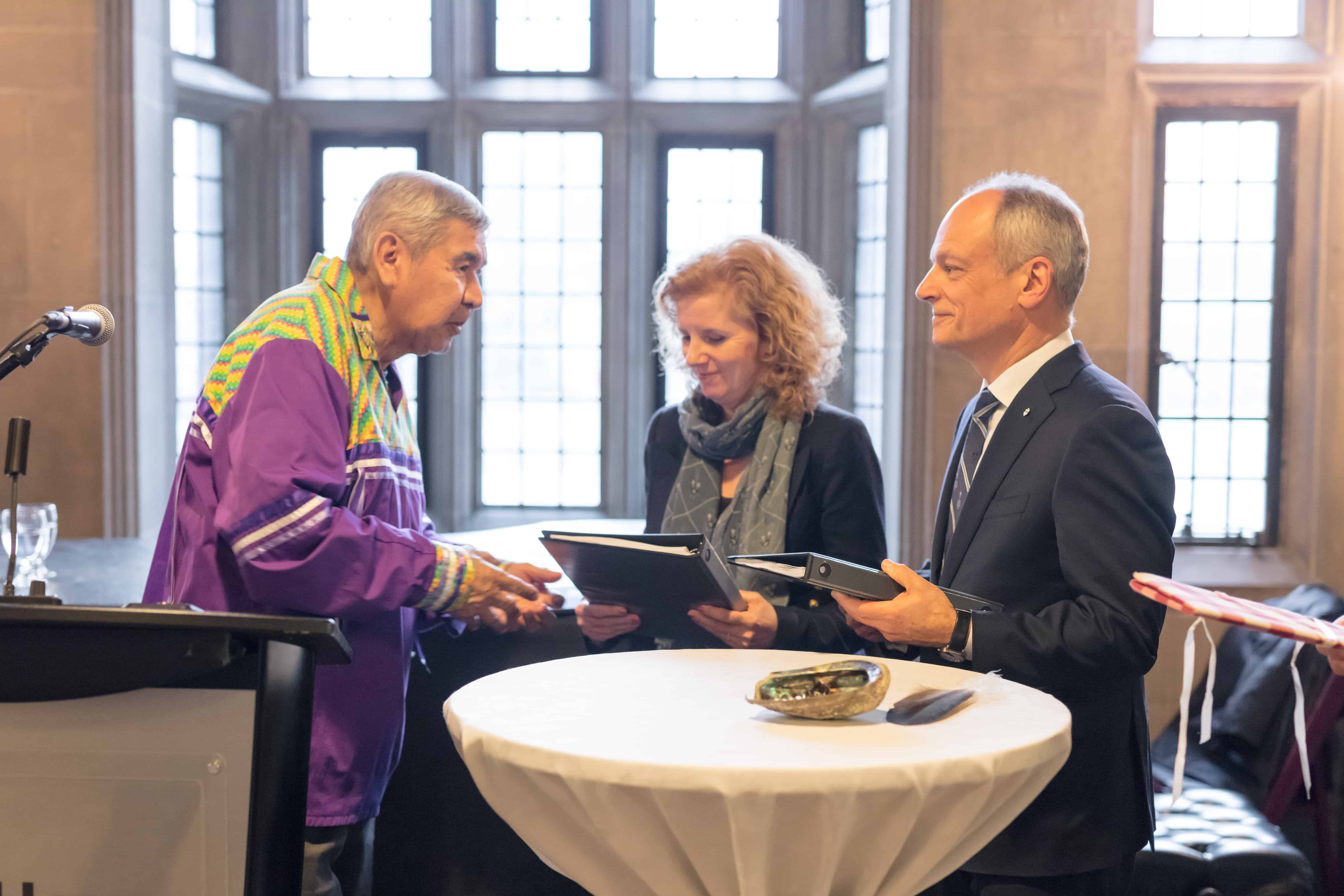 Elder Andrew Wesley gives Provost Cheryl Regehr and President Meric Gertler the TRC report in January 2017.