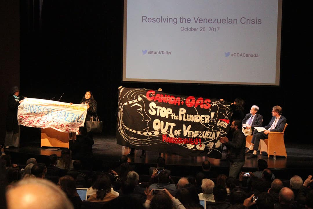 """Activists against Canadian intervention protest on stage at the """"Resolving the Venezuelan Crisis"""" event.ALEX TOUGH/THE VARSITY"""
