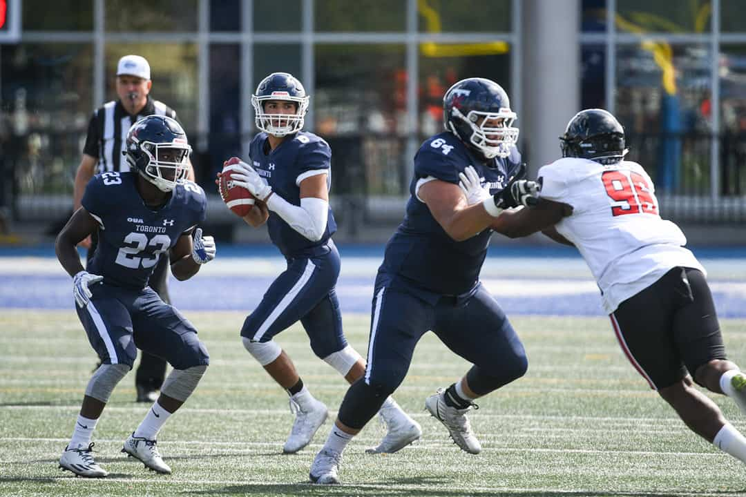 Blues quarterback Clay Sequeira looks for an open receiver. MARTIN BAZYL, COURTESY OF THE VARSITY BLUES