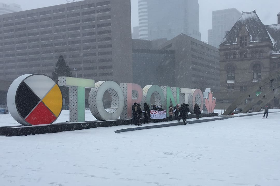 Protestors gathered at Nathan Phillips Square before marching in heavy snow.  KHATCHIG AINTEBLIAN/THE VARSITY